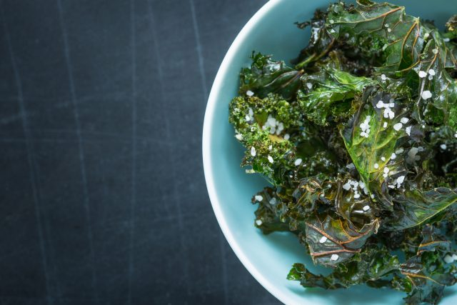 Kale chips with salt in pastel blue bowl captured from above (top view)