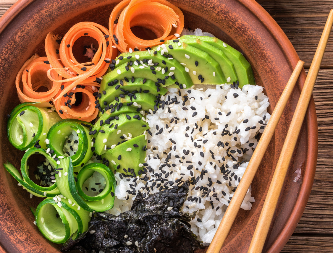 Sushi bowl with seaweed, avocado, radishes, cucumber and black